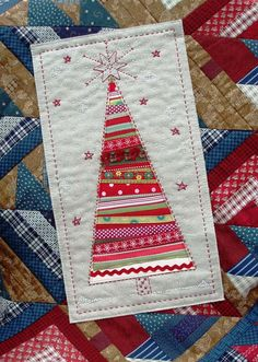 Currently trying a tree like this as a centerpiece for one of my quilts but with more blue. She also has snowmen on there! Ribbon Tree Sunburnt Quilts