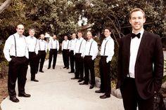 Groom in black suit, groomsmen in black pants and suspenders, kind of look like waiters