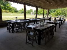 Long farm tables with cheese cloth material for runner with lantern, two candlesticks and doilies down the sides.