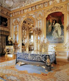 Gilded room in Versailles with portrait of Louis XIV.