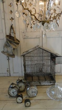 this is so much of what I like.  Chandelier, wire birdcage, old clocks very nice