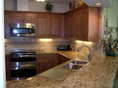 The Fairmont door from CliqStudios is in the inset cabinetry style. The cabinets are finished in the Maple Caramel Jute Glaze. Kitchen features a nice granite counter, tile backsplash, and crown molding.