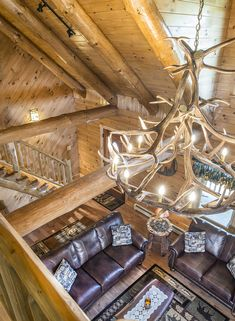 The balcony of this log home overlooks the great room and showcases cathedral ceilings, exposed beams, an antler chandelier, and more! #loghomes #logcabins #loghome #logcabin