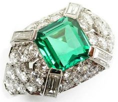 Mid-century emerald and diamond ring, circa 1950. Centered by a trap-cut emerald surrounded by diamonds with radiating baguette diamond at each corner.