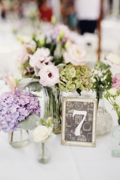 simple and small little flowers scattered around a lantern or candleabra or set of pillar candles as centerpiece