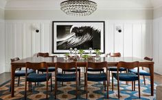 """Why we love it:  The large-scale art makes a dramatic focal point.  Behind the design: """"Everything came together around the vintage N.O. Møller chairs,"""" Nelson says. She echoed the curved backs in the organic pattern of the rug and designed the mahogany table to complement the wood of the frames."""