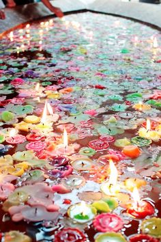 This would be a really cool backyard feature: a canoe filled with water and rainbow tea lights.
