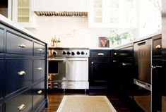 Black painted kitchen cabinets + brass Vernon bin pulls from Rejuvenation.
