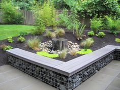 simple water feature. rock and wire wall with sitting bench