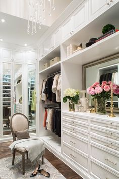 A demure Louis XIV-style chair provides a perfect perch for putting on shoes in this glamorous custom closet in a London loft. Cabinetry and shelving extend to the ceiling to maximize storage. Meanwhile, an elegant vanity offers display space for decorative and functional accessories in the transitional space.
