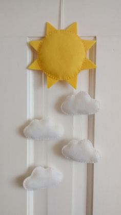 Add some sunshine all year round to you little ones nursery, with this bright Sun & Clouds hanging decoration. Designed, cut and hand sewn by me from soft felt, and lightly filled with polyester filling. Measurements: Sun: 6½ / 16 cm Diameter Clouds: 3½ / 9 cm wide Overall length including hanging loop: 16½ / 42cm Safety: This product is not a toy and is designed for decorative use only.