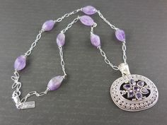 "Made with genuine amethyst gemstones, sterling silver pendant, chain, and lobster clasp. Measures 23"" inches in length. Can be adjustable."
