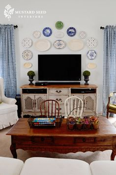 One way to camouflage your TV out-in-the-open is to fill the wall around it with art.  In this case, Miss Mustard Seed hung a collection of plates.  She also added a pair of topiaries to flank the TV on the cabinet.