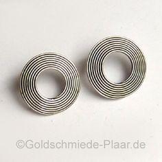 Kreisrunde Ohrstecker aus Silber (925/-) mit feinen Rillen. Die Rillen sind geschwärzt, die erhabenden Stellen im Kontrast dazu poliert.
