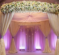 The walls behind this Chuppah/Mandap are draped with white fabric and up lighted with purple. Round chuppah draped with white fabric and ceiling gathered in the center. Huge floral display on top. Wedding Mandap, Uplighting Wedding, Wedding Henna, Wedding Backdrops, Wedding Ceremony, Wedding Stage Decorations, Engagement Decorations, Pipe And Drape, Wedding Invitation Kits