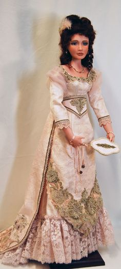 Priscilla 2/5 Description: Evening ensemble circa l893. Pale mauve silk jacquard, lace and bead embellished gown with train. Aigrette, ornate paddle fan and high heel court slippers. 24 inches, mohair wig and painted eyes.