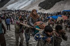 A Hindu pilgrim is carried on a palanquin by Kashmiri bearers over a glacier on her way to the sacred Amarnath Cave, June 29, 2012. More than 700,000 Hindu pilgrims are expected to take part in this year's two-month pilgrimage, according to local officials. (Daniel Berehulak/Getty Images) #