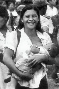"""""""Miliciana de Waswalito"""". Comenzamos con una fotografía icónica, un símbolo visual de la revolución, una imagen muy popular y difundida por todo lo que representa: la mujer miliciana que amamanta a su bebé mientras lleva su fusil al hombro."""