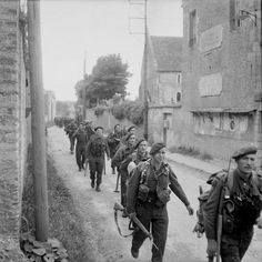 Soldiers of the 45 Commando Royal Marines, attached to 3rd Infantry Division for the assault on Sword Beach, pass through a street of Colleville-sur-Orne, 10 Km NE from Caen, on their way to relieve forces at Pegasus Bridge. Normandy, France. 6 June 1944.