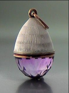 Faberge: white guilloche enamel and faceted amethyst egg pendant with gold mounts, workmaster Feodor Afanasiev