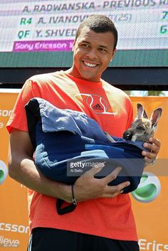 Jo-Wilfried Tsonga of France stands on stage with animals from the Miami Zoo during day eight of the 2010 Sony Ericsson Open at Crandon Park Tennis Center on March 30, 2010 in Key Biscayne, Florida.