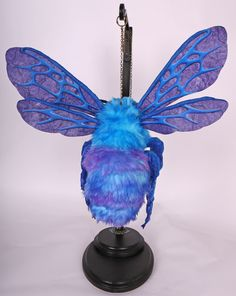 Blue Monday 2016 Mixed Media flying sculpture 15x10x10 with base 7x9x23. This work can hang from a ceiling hook, curtain rod, wall bracket, or provided sculpture base. Decorative chain is removable.