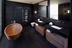 moderne badezimmer mit schwarzen wänden_schwarze fliesen im bad und freistehende badewanne aus holz