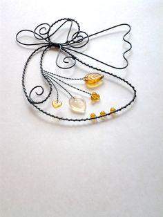 Andělka+v+medové+Drátovaný+andělíček +z+černého+vázacího+drátu,+dozdobený+skleněnými +medověhnědými+kuličkami +a+medovými+a+béžovočirým+skleněným+lístečkem.+Vhodný+k+zavěšení+na+zeď,+dveře,+skříň,+lustr....+Velikost+andílka+: +15 +cm+x+12+cm,+++háček