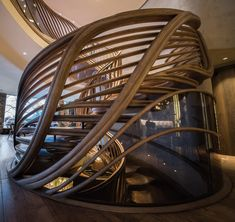 """Atmos Studio's spiralling timber staircase features """"leaf-like"""" stairs that emerge from a structural stem; as featured at https://www.dezeen.com/2018/04/27/atmos-studios-timber-staircase-london-restaurant/"""