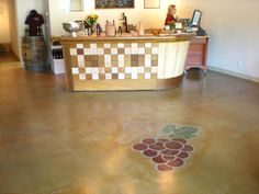 Another custom NW Concrete decorative concrete stain project with an integrated stenciled grape design image for a commercial floor.