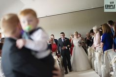 The groom watches on as his beautiful bride walks down the aisle towards him & their son. Weddings with kids.Weddings at Druids Glen Resort photographed by Couple Photography www.couple.ie