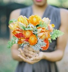 The bridesmaids will carry clutch bouquets of yellow hydrangeas, orange ranunculus, orange freesia, orange parrot tulips, pale green succulents, green maiden hair ferns, and grey dusty miller wrapped in yellow-gold ribbon.