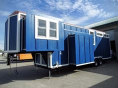 This is a Carpathian tiny house with slide outs by Tiny Idahomes. From the outside, you'll notice the house sits on a long fifth wheel trailer and features blue board and batten siding and wh…