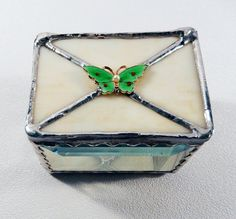 Decorative Stained Glass Box, Jewelry, Keepsake, Memento Box, Blue, Green Butterfly with red dots and small pearl, glass bevels, mirror bottom. The perfect gift for yourself or someone special! This small, one of a kind box can be used for so many things, jewelry, paperclips, stamps etc. The sides are beveled glass, bottom is mirrored glass, the top is a bone colored Artglass along with a vintage enameled brass bright green (this years Pantone color) butterfly with red dots on its wings…