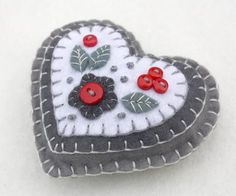Handmade felt heart with applique and embroidery in red, white and grey, embellished with tiny buttons. A perfect Christmas gift or decoration . 9cm x 8cm approx, with a cotton loop for hanging.
