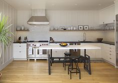 """For an urban farmhouse look, Davis applied classic board-and-batten paneling to the 265-square-foot space. """"It breaks up the formality and allows a modern remodel to blend nicely with the historic bones of the house,"""" says designer Elsa Brown, a member of Davis's team. #modernremodeling"""