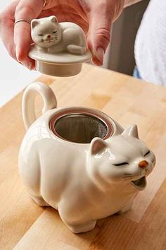 Big Cat teapot ... large white cat with closed eyes, yawning open mouth as spout and tail as handle, small sleeping kitten on its back as knob, w/ wire mesh basket strainer, ceramic and stainless steel