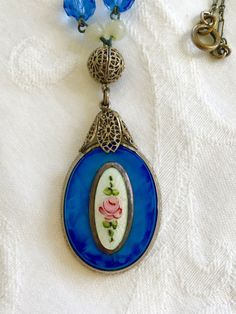 Art Deco Necklace, Blue Glass Pendant, Guilloche Panel, Glass and Moonstone Beads, Silver Filigree  This is a stunning art deco filigree necklace with blue glass pendant with center guilloche enamel panel framed in silver. The pendant is topped with a silvertone filigree ball with moonstone and glass faceted beads. It is in wonderful vintage condition. The necklace is 15 and the pendant is 1 1/2 x 1 without the filigree leaves on top.  More necklaces https://www.etsy.com/y...