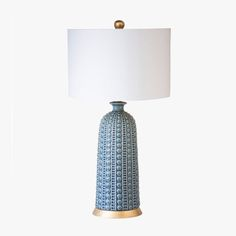 Tapered ceramic urn shaped lamp in a beautiful varied blue glaze placed upon a simple metal base in gold leaf. Topped with a white linen shade.