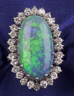 Black Opal and Diamond Ring, prong-set with an oval cabochon opal measuring approx. 21.60 x 11.30 x 5.65 mm, framed by twenty-eight full-cut diamond melee, approx. total diamond wt. 1.12 cts., 14kt white gold mount, size 6. Skinner.