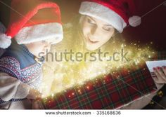Christmas holiday! Mother with baby opens the magic box with gift. Box full of magic surprises and secrets! The kid looking at the box with interest. Mom and baby in Santa hats. Happy family concept