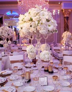 Centerpiece of white hydrangeas, roses and lilies in a tall glass vase. Check out the additional white hydrangeas that are dangling like earrings.
