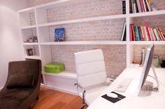 Este escritório foi projetado por Lucila Martens para uma mulher solteira. Para que o ambiente de 10 m² fosse ampliado, a arquiteta optou por tons escuros somente na chaise-longue. A estante e a mesa foram revestidas de laca branca. A parede de tijolinho apresenta uma pintura lavada, também branca. O piso é assoalho de madeira grápia.