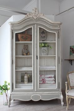 French armoire painted grey and white with chicken wire screening repurposed as a display cabinet
