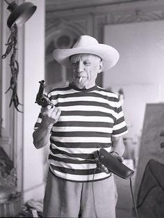 Pablo Picasso with Gary Cooper's gun and hat, photographed by André Villers in 1959.