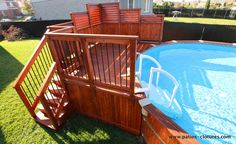 cedar above ground pool deck with privacy screens and staircase partially integrated into the deck so that it does not occupy too much space in the yard