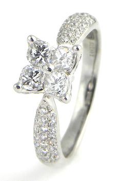 Four calla diamonds are prong set in the center with round diamonds bead set into three rows on each side of the band and into the outside butterfly design.