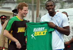 Britain's Prince Harry, left, receives a T-shirt as a gift from Olympic sprint…