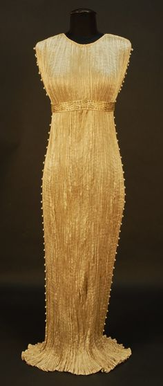 "Gold silk 1920s Fortuny gown. The iconic ""Delpho"" dress. Empire waist column gown with jewel neck. These dresses were made of silk so light that glass beads hand-blown in Italy were placed down the sides to weight it down. Fortuny did all the pleating by hand himself and no one has ever been able to replicate how perfectly he did it. Photo: Charles A. Whitaker Auction"