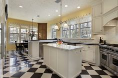 Large kitchen with black and white checkered floor and yellow walls.  Rest of kitchen built with white cabinets and chef-grade stainless steel appliances.